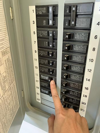 This picture shows an electrical panel installation with upgrade to 200 Amp in Santa Barbara. The electrician is pointing at the circuit breaker to show the new panel